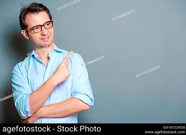 Handsome man on gray background pointing copy space