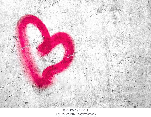 Pink heart hand drawn on concrete wall
