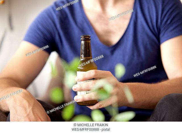 Man's hand holding beer bottle