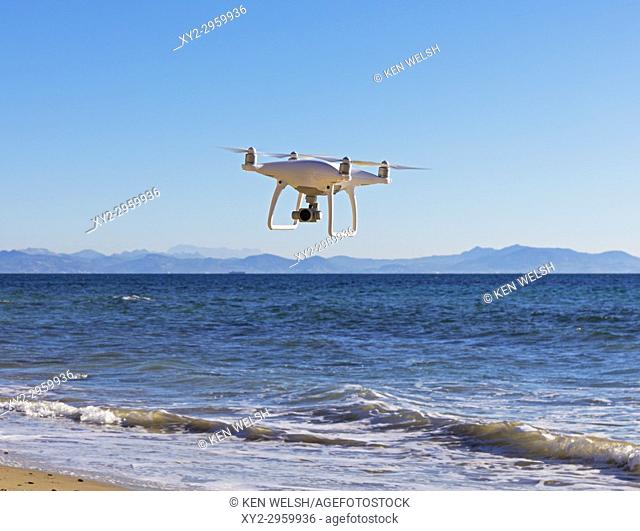 DJI Phantom 4 drone with camera inflight over sea. Coast of Morocco in background
