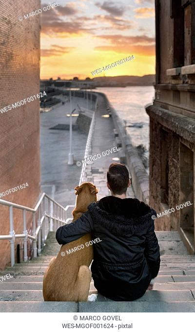 Spain, Gijon, back view of man and his dog sitting on stairs watching sunset