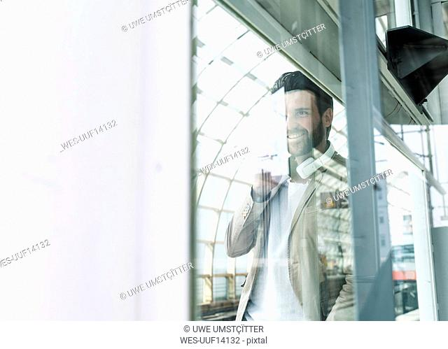 Smiling young man behind glass pane at the station platform