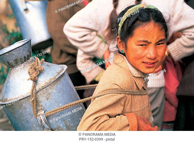 Girl carrying steel pot with rope