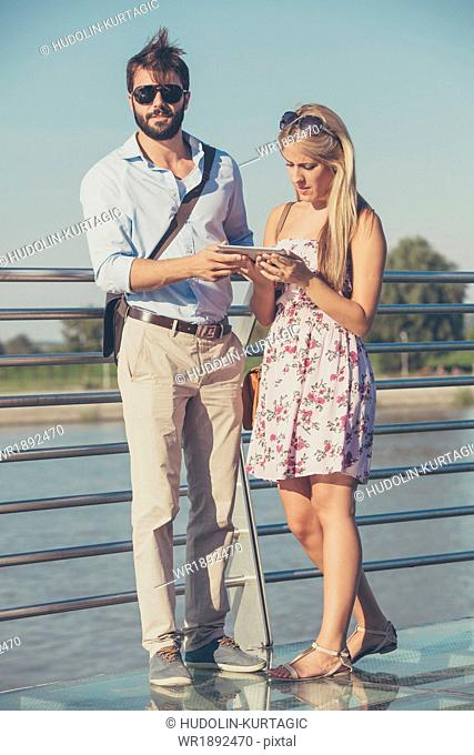 Young couple with digital tablet on sightseeing tour