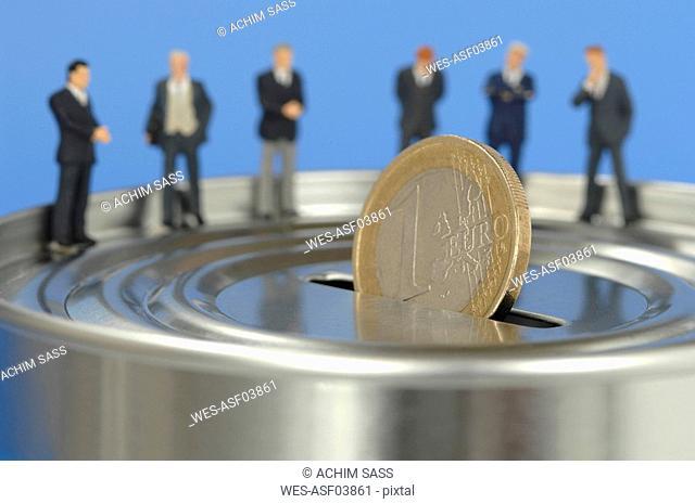 Business men figurines standing on money box