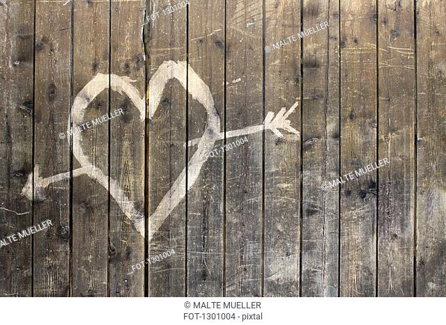 Heart shape with arrow symbol on wooden fence