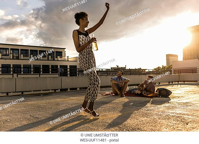 Young woman dancing on a rooftop party