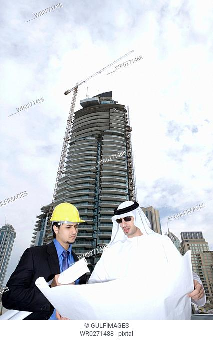 Businessmen looking at blueprints at construction site