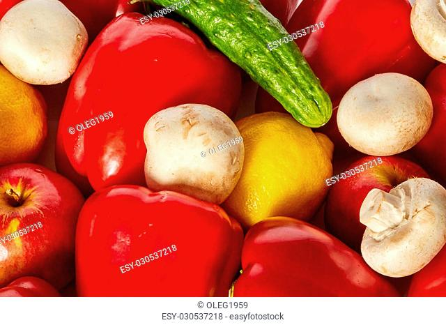 Many sweet ripe vegetable, fruits and mushrooms are on a white background. Close up