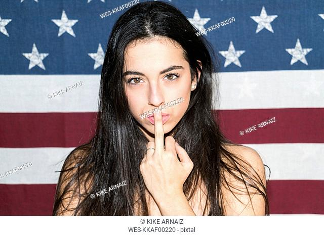 Young woman standing in front of US flag, making naughty hand sign