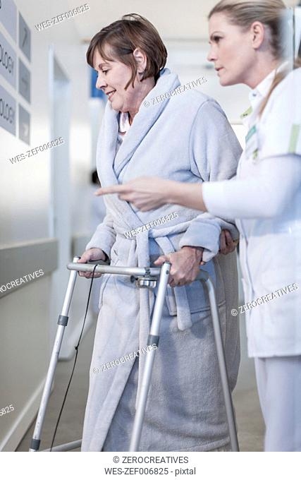 Nurse helping patient with walking frame in hospital corridor