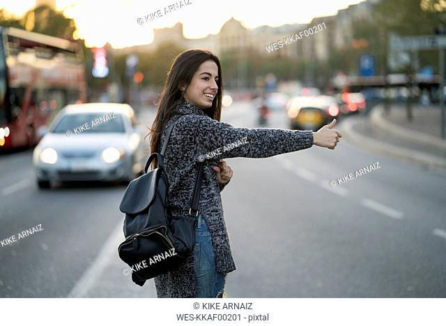 Smiling young woman hitchhiking on urban street