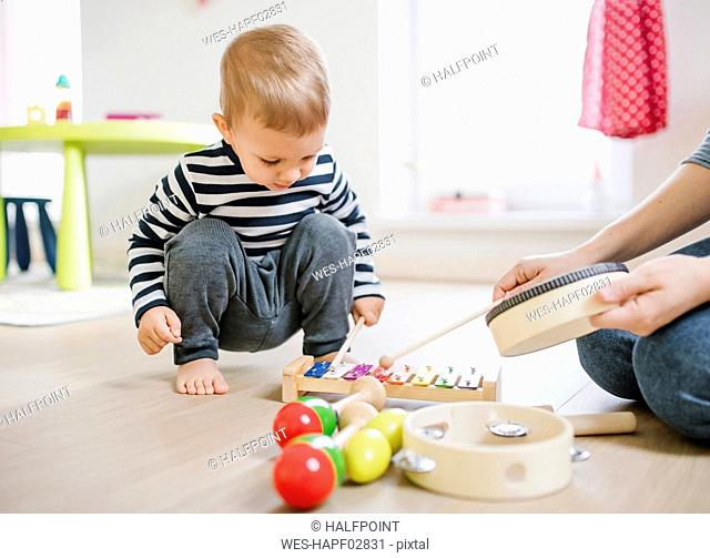 Mother and toddler son playing with musical instruments at home