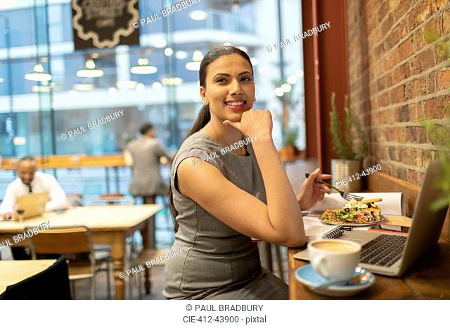 Confident businesswoman eating lunch and working in cafe
