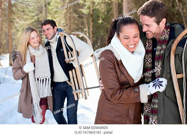 Portrait of smiling couple with sled in snowy woods