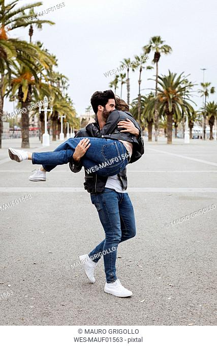 Spain, Barcelona, happy young man carrying girlfriend on promenade with palms