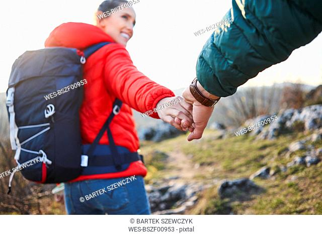 Close-up of couple holding hands on a hiking trip in the mountains