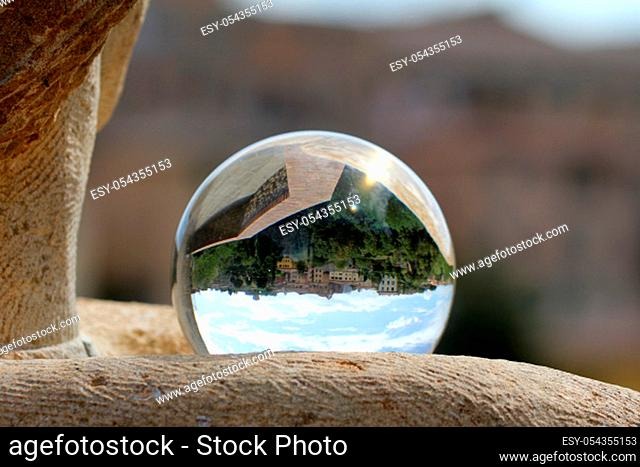 The world is upside down, old town of Volterra seen through the glass ball