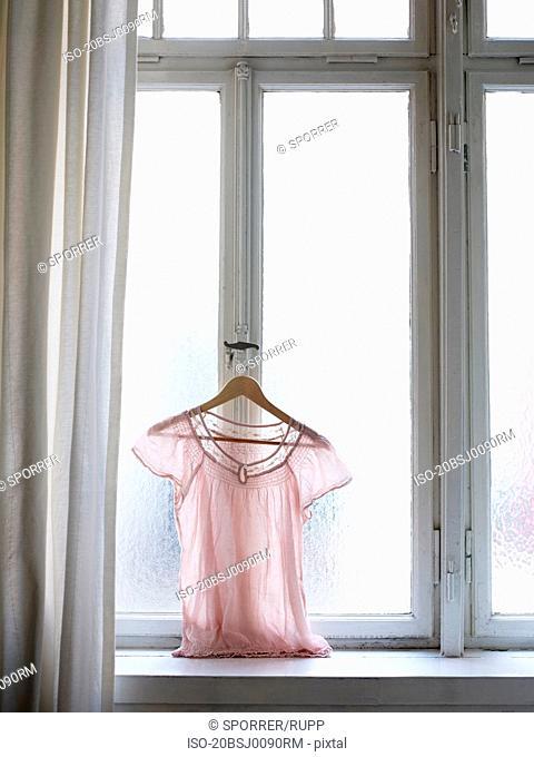 Blouse hanging on window