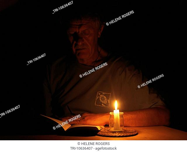Man Reading Book By Candlelight During a Power Cut