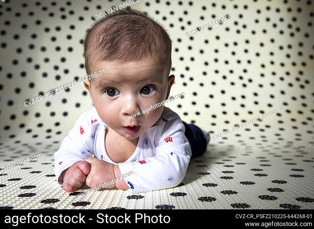 Infant child looking with curiosity while lying on tummy in nursery