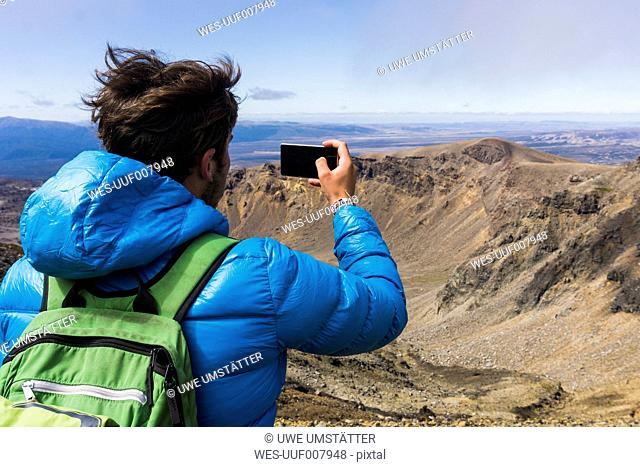 New Zealand, Tongariro National Park, back view of hiker taking a photo with smartphone