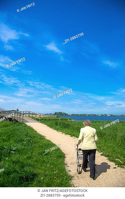 old woman walking with help on footpath in holland