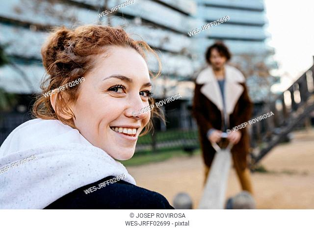 Portrait of happy young woman with boyfriend on a seesaw at a playground
