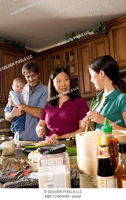 Asian-Caucasian family preparing dinner together