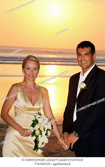 wedding couple on the beach with sunset view in the background