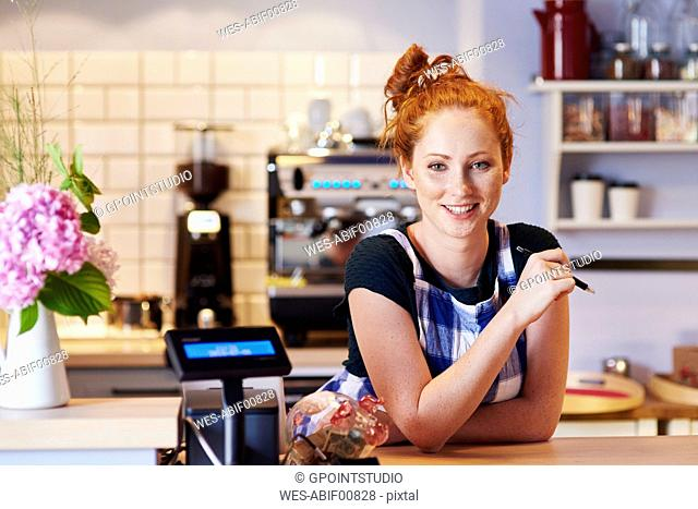 Portrait of smiling young woman at the counter in a cafe