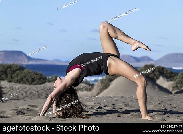 Side view of slim woman in crab posture with leg raised training yoga on sandy beach in sunshine