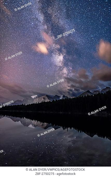 The summer Milky Way in portrait orientation over Herbert Lake and Mount Temple and peaks around Lake Louise, in Banff National Park, Alberta