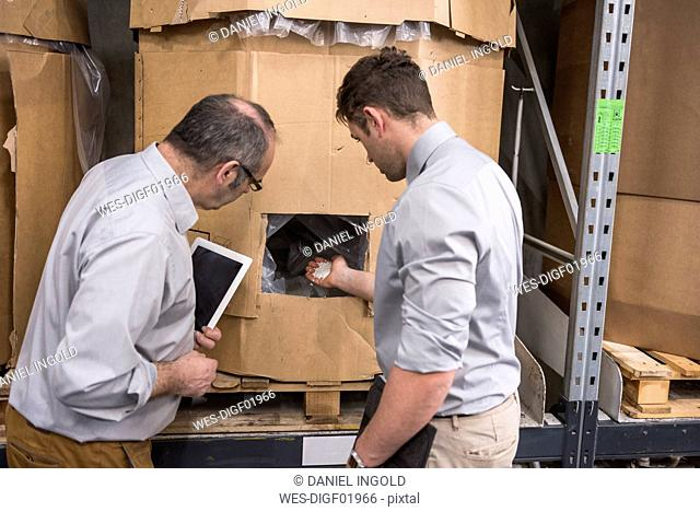 Two men examining product in factory warehouse