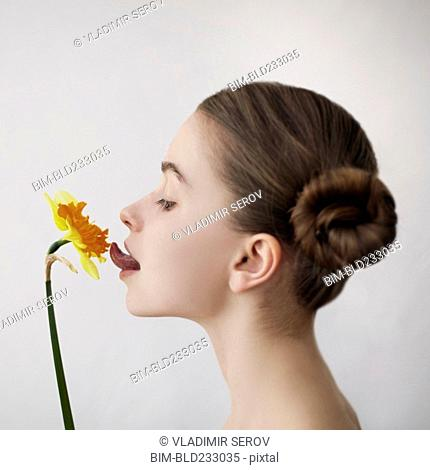 Caucasian girl licking yellow flower