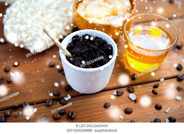 beauty, spa, bodycare, bath and natural cosmetics concept - homemade coffee scrub in cup and honey on wooden table over snow