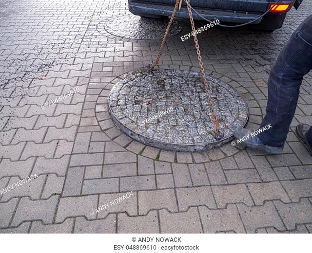 Unrecognizable municipal utility worker opening a heavy double manhole cover on a road paved with concrete paving stones