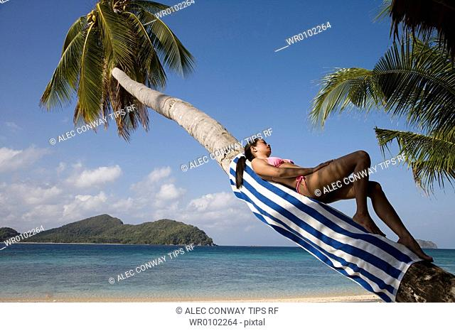 Philippines, El Nido bay. Philippino woman lying on palm tree trunk
