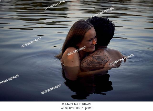 Romantic couple embracing in lake at sunset
