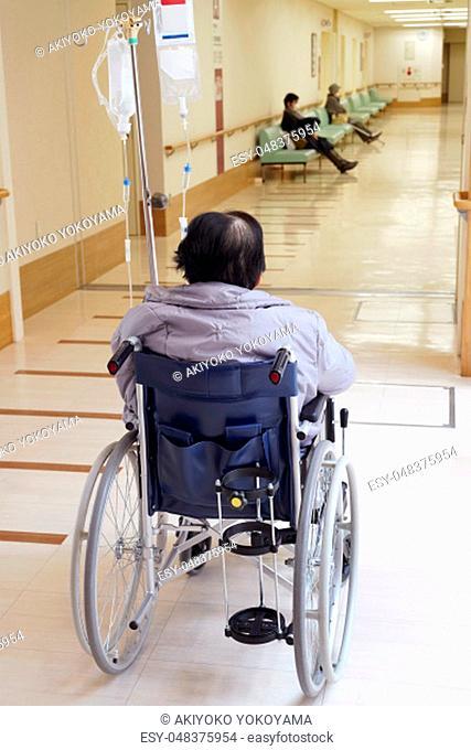 Back view of senior or elderly woman on wheelchair at hospital hallway