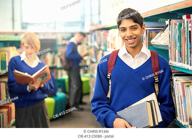 Portrait of teenage student standing with books in college library