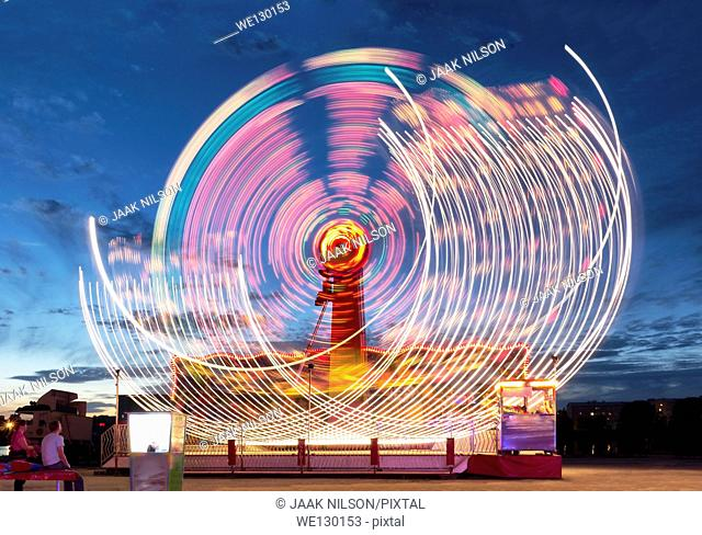 Lighted ferris wheel in amusement park at night. Illuminated attraction in the move