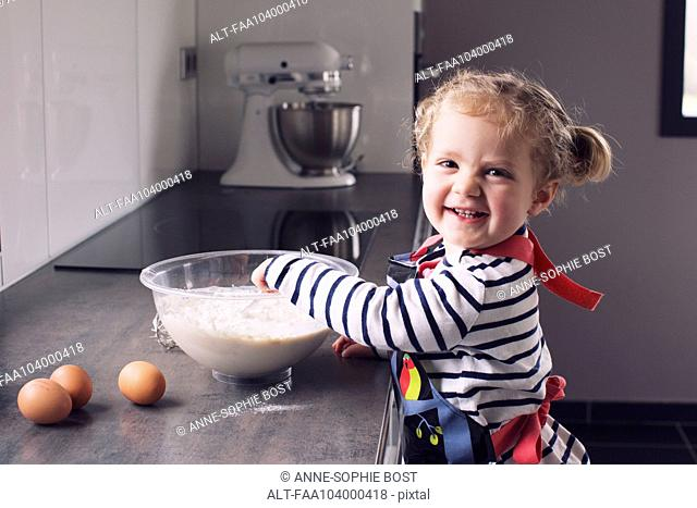 Little girl mixing batter, smiling, portrait