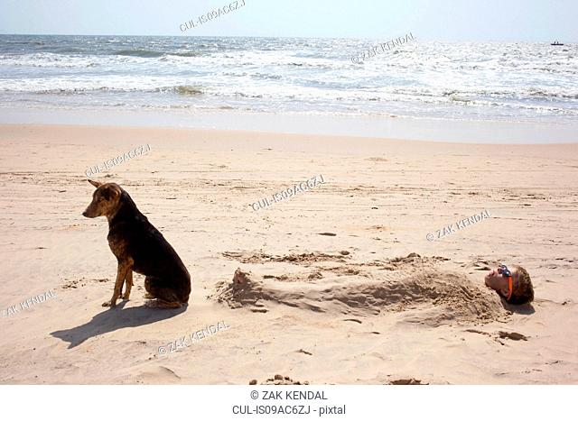 Boy buried in sand on beach with dog