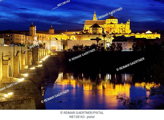Cordoba Cathedral Mosque reflected in Guadalquivir River with Roman Bridge at twilight