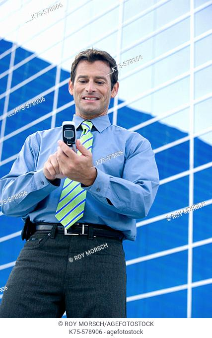 Man text messaging on cell phone outside office building