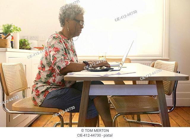 Senior woman paying bills at laptop in kitchen