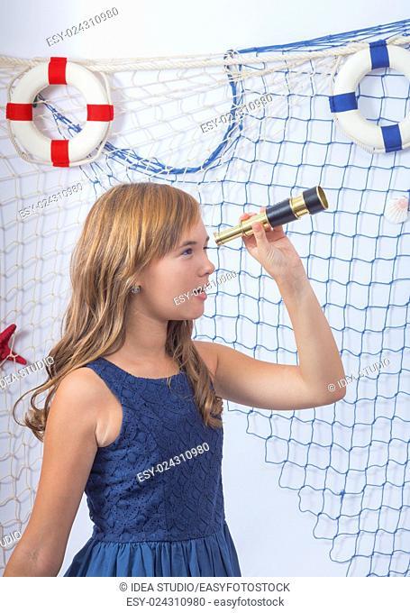 Beautiful teen girl in blue dress looking at telescope