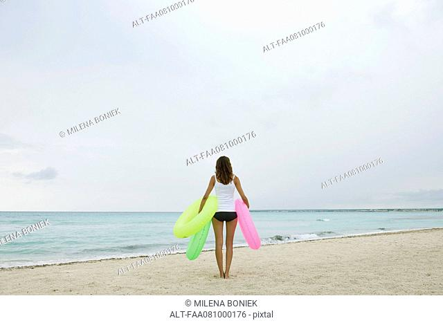 Woman standing on beach, holding inflatable rings, rear view