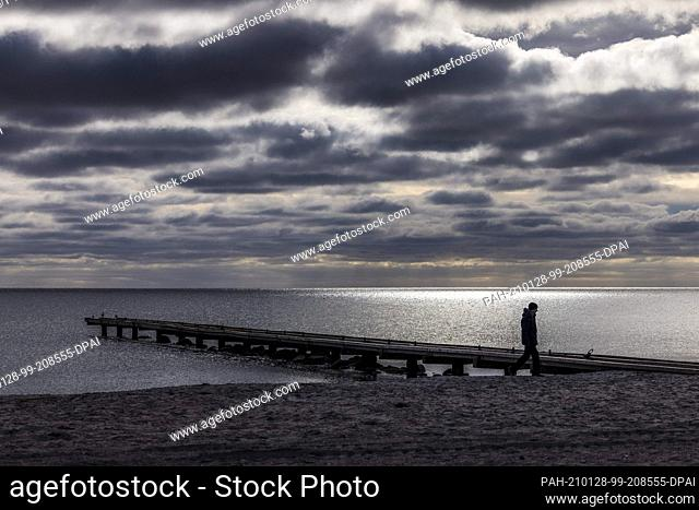 28 January 2021, Schleswig-Holstein, Insel Fehmarn: A man walks under dark clouds on the south beach. Photo: Frank Molter/dpa